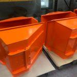 Orange powder coated digger buckets